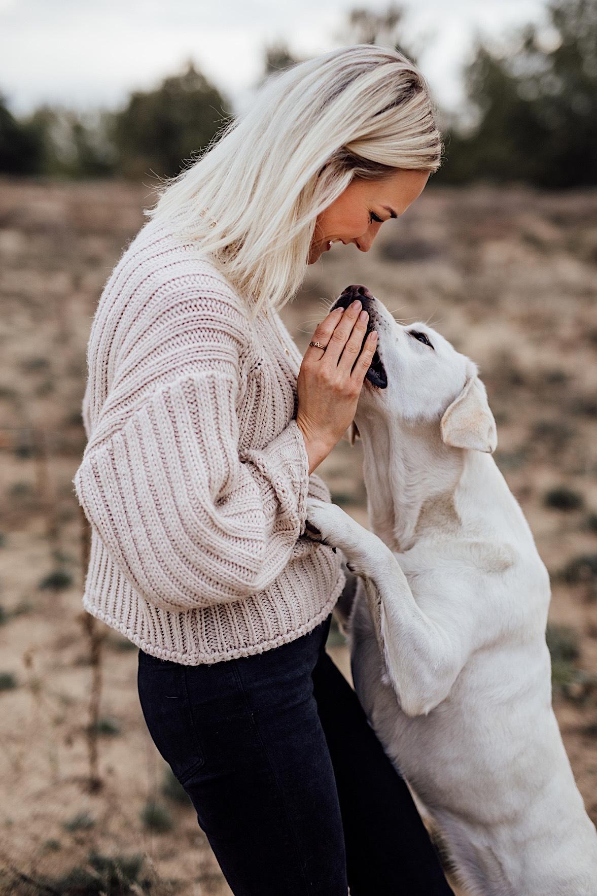 Hund springt freudig an Frau hoch, Frau lächelt Hund zu