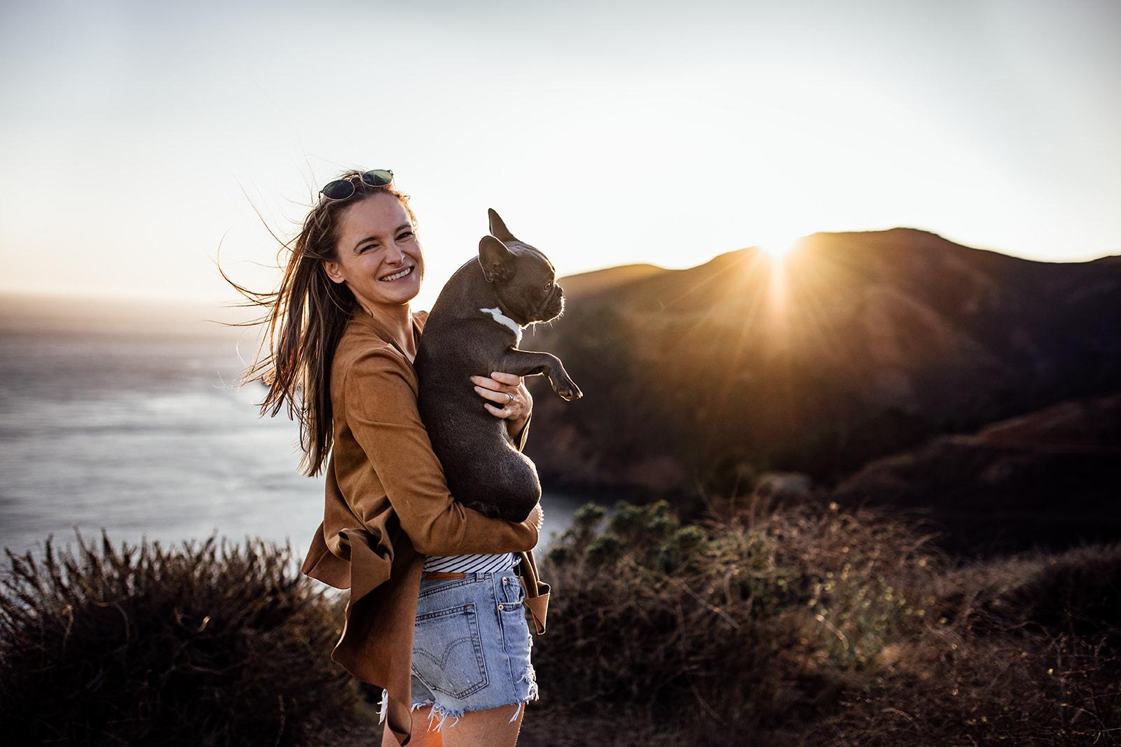 Frau steht mit kleinem Hund am Hügel und schaut über das Meer dem Sonnenuntergang entgegen