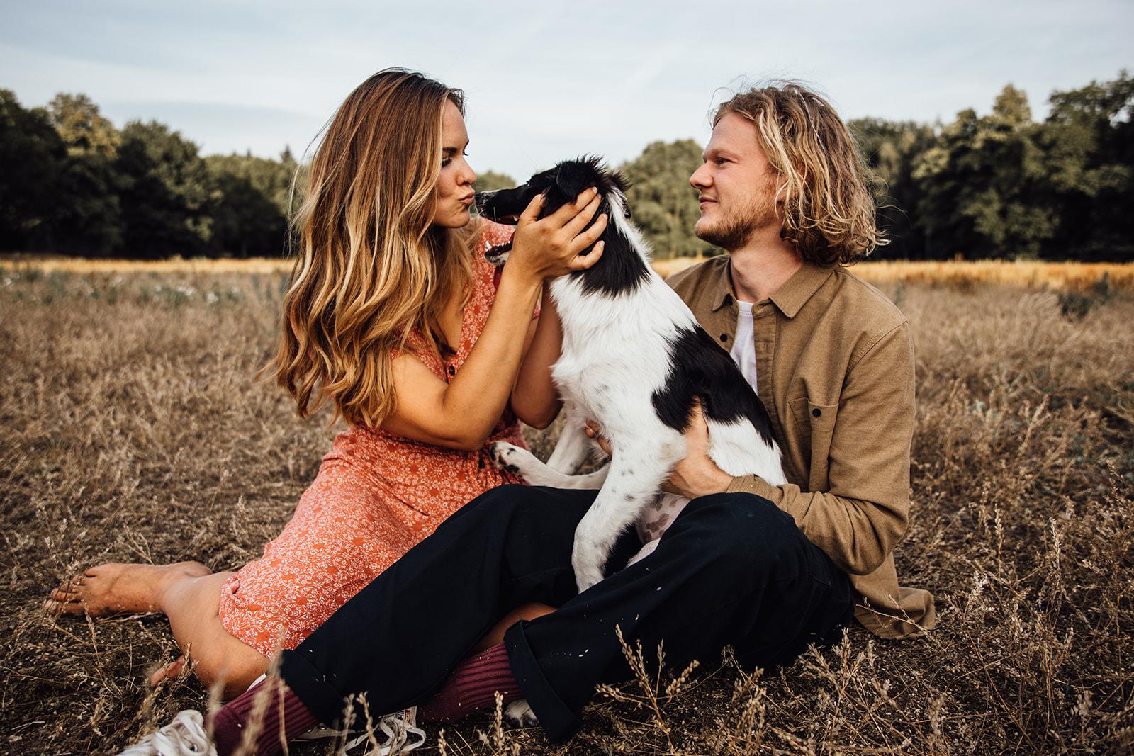 Paar sitzt mit Hund auf einer Wiese