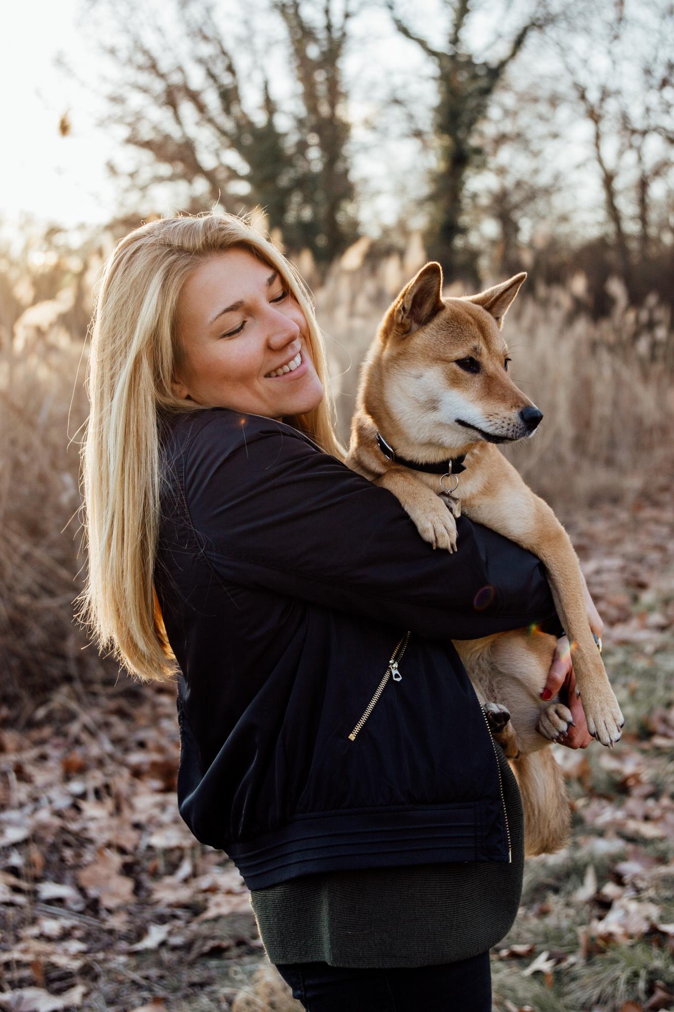 Frau hat Hund, Shiba Inu, auf dem Arm, Laub am Boden