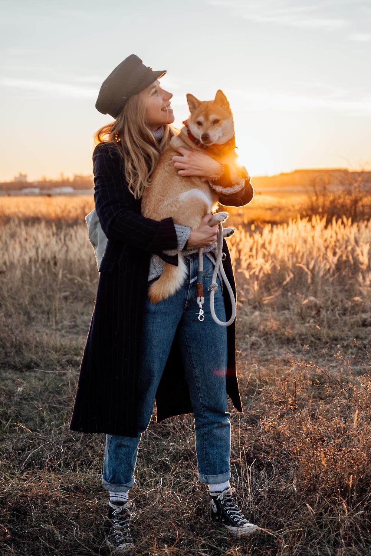 Frau und Hund stehen auf dem Feld, Hund auf dem Arm der Frau, Sonnenuntergang im Hintergrund
