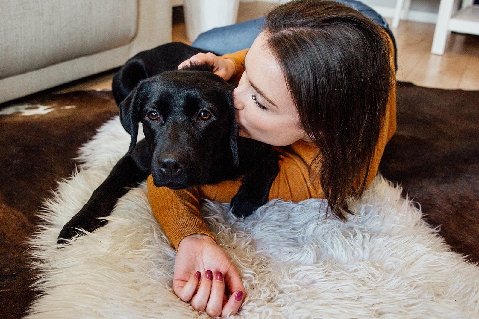 Frau liegt mit Hund am Boden und küsst diesen an den Kopf, Hundefotoshooting in Berlin Homestory